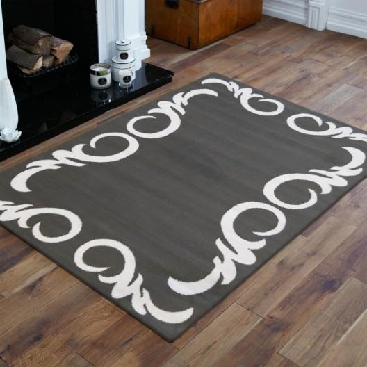Elegantný koberec v sivej farbe s bielym ornamentom