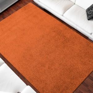 Jednofarebný koberec oranžovej farby